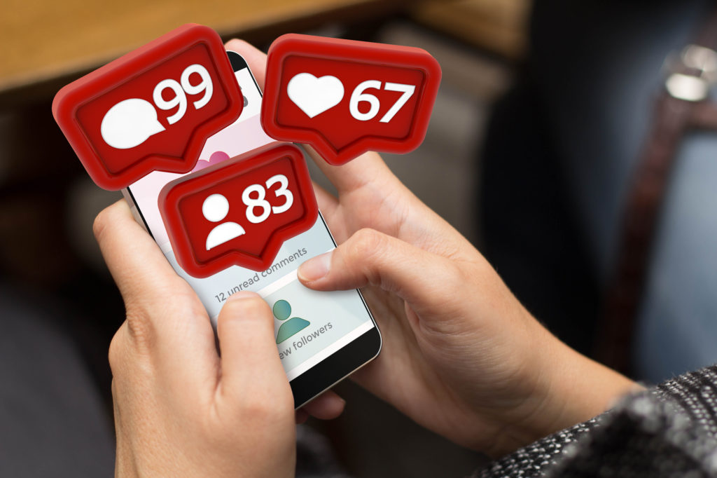Closeup over the shoulder view of two hands holding a smartphone. Social media icons rise from the screen showing 99 comments, 67 likes, and 83 followers.