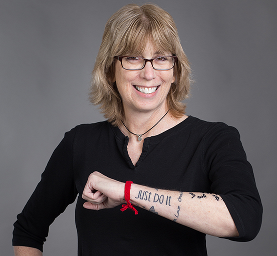 Madalyn smiling in a black elbow-length t-shirt. She holds up her forearm showing her tattoo which reads just do it. A red ribbon is tied around her wrist.
