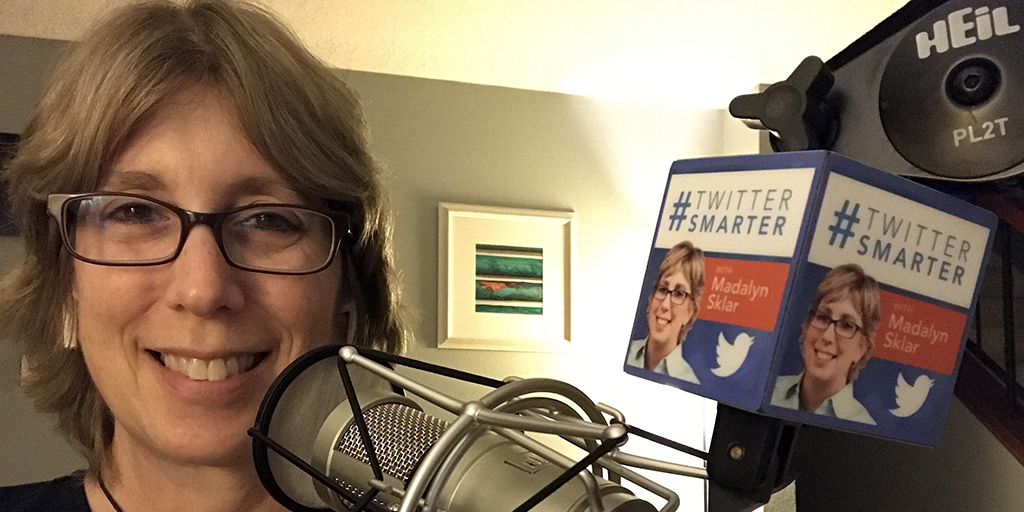 Headshot of Madalyn smiling in front of a podcast microphone. Also in view is the Twitter Smarter mic flag with Madalyn's photo and Twitter logo on it.