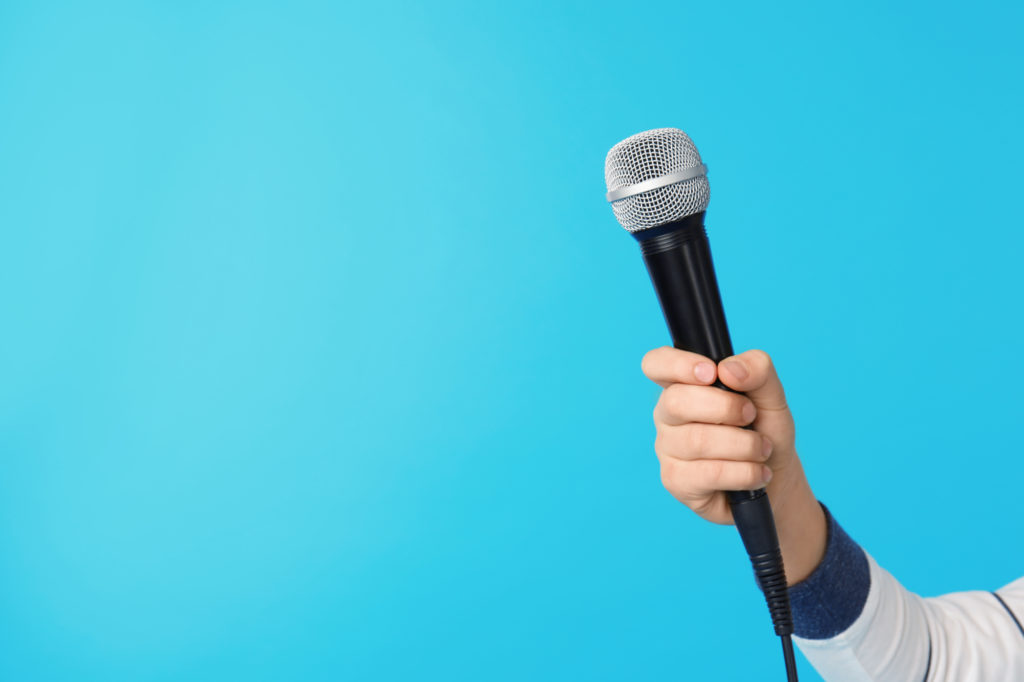 Hand holding a microphone against blue background