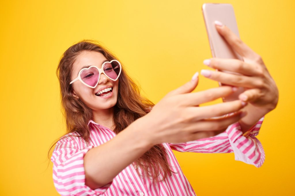 Woman wearing rose colored, heart shaped glasses and pink and white striped shirt holds smartphone at arms length and laughs.