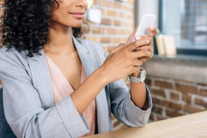 Cropped view of African American casual business woman using smartphone