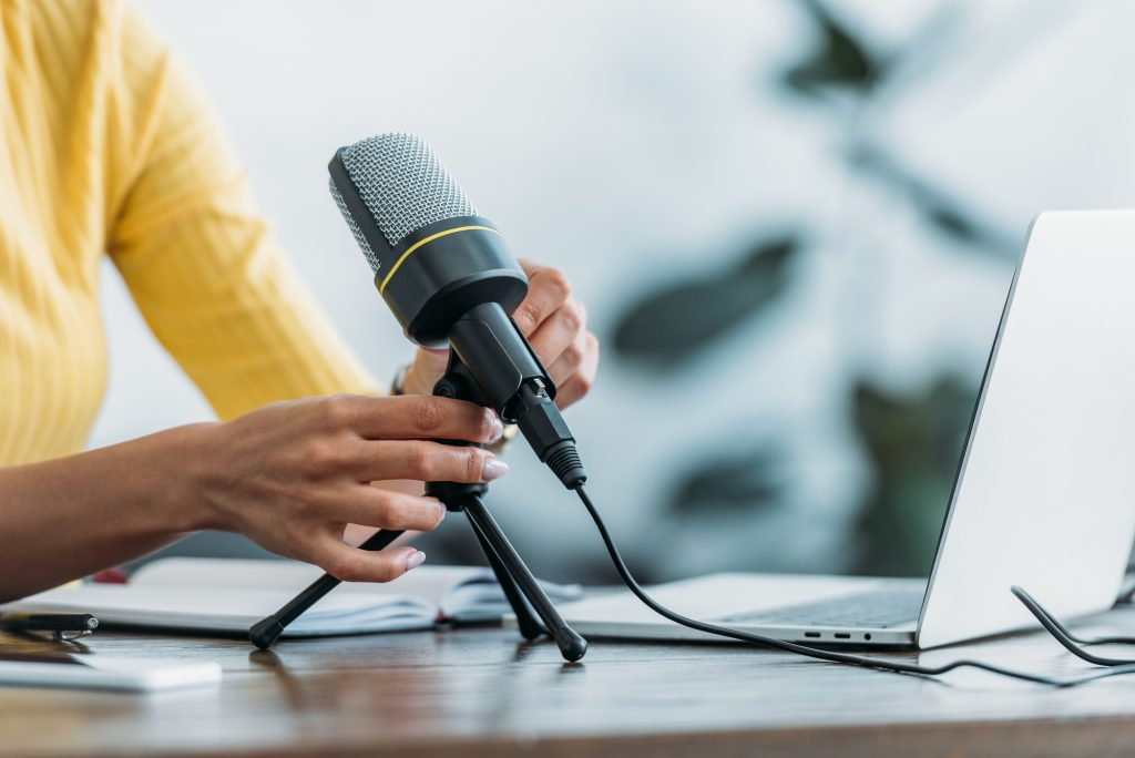 Closeup of woman's hands holding microphone attached to tripod on desk next to laptop computer.