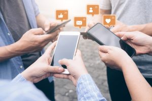 People stand in a circle. Digital icons such as likes and email float from the smartphones they hold.