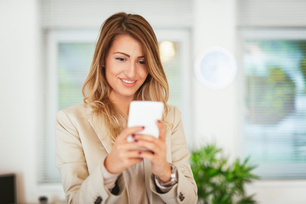 Business woman in her office using her smartphone and smiling.