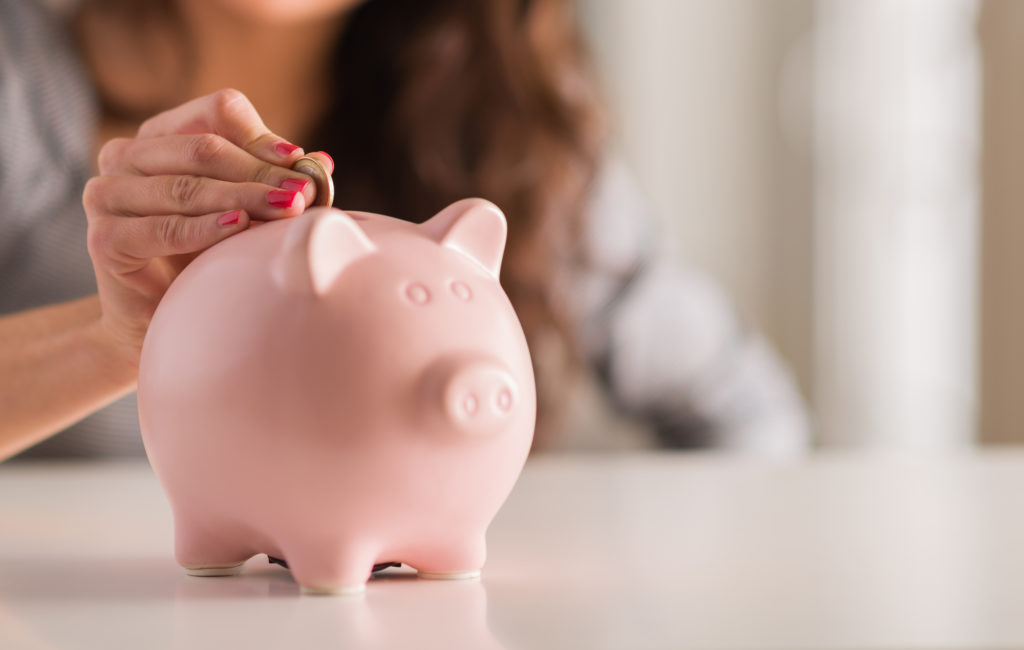 Woman putting coins into a pink piggy bank.
