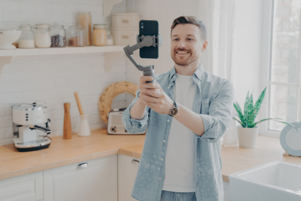 A smiling man stands in his kitchen filming himself on his smartphone using a handheld tripod.