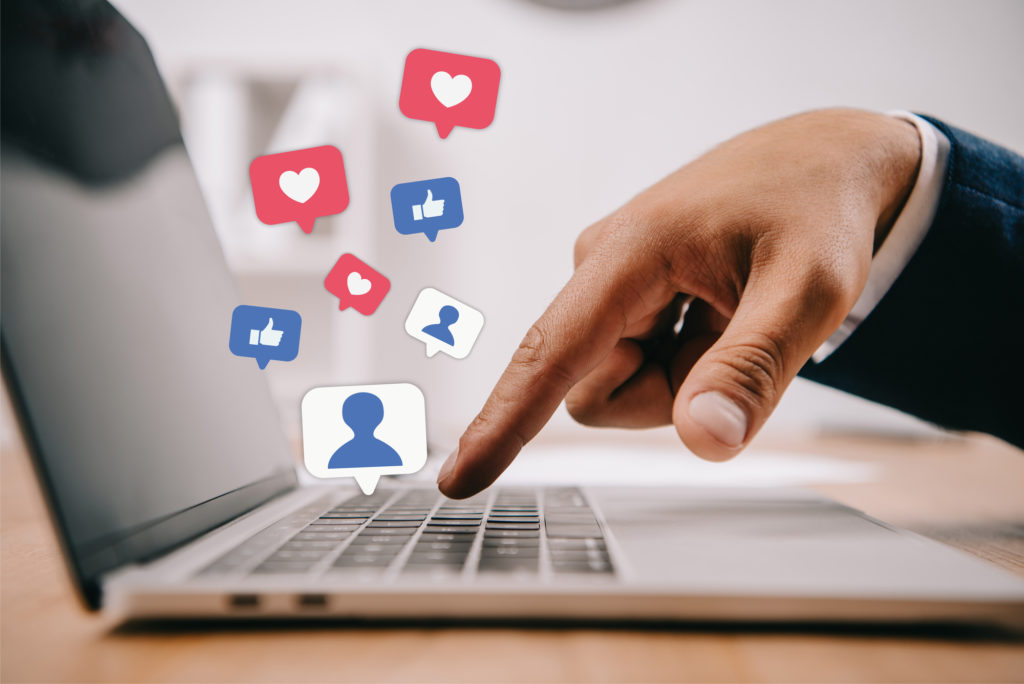 Closeup of a hand pointing at the keyboard of a laptop computer. Social media icons representing followers and likes float up from the keyboard.