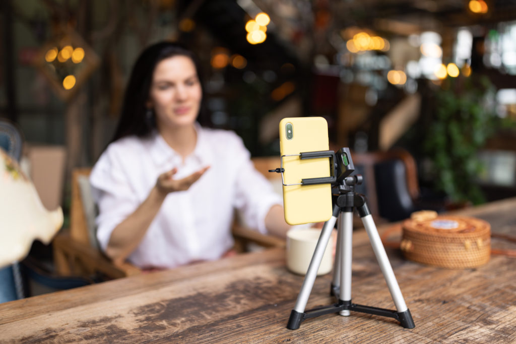 A woman sits at a table filming herself on a smartphone attached to tripod standing on the table.