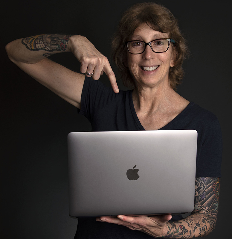 Photo of Madalyn Sklar holding a laptop and pointing to it.