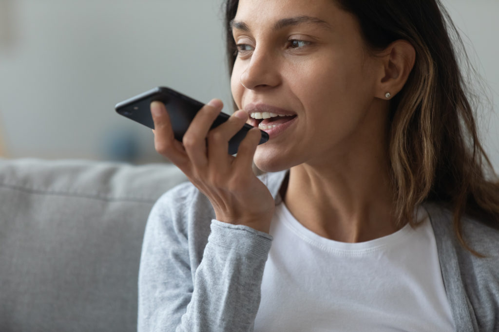 A woman speaks into a smartphone, holding the bottom of the device toward her mouth.